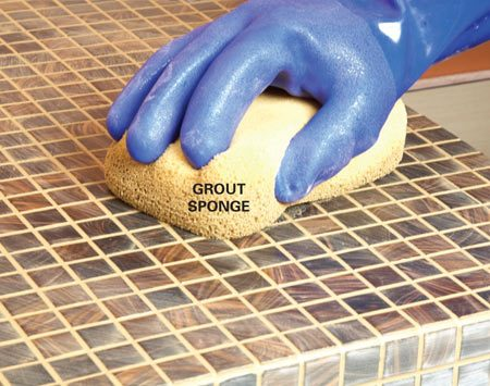 "<b>Photo 8: ""Tool"" the grout with a damp sponge</b></br> Wait until the grout starts to set up before tooling. Wring out the sponge until it's just damp. Then rub it over the tile in a circular motion to smooth and shape the grout and fill tiny voids and pinholes."