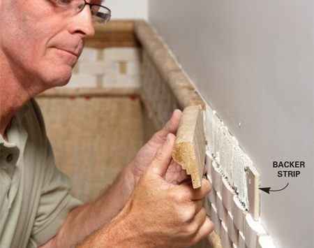 "<b>Depth adjustment</b></br> <p>If you're using tile  trim, it's often necessary to ""build out"" the trim   so it protrudes from the field tile. A strip of tile backer   can help you get the  build-out just right. Any kind of backer board   will do; just slather one  side with thin-set or mastic and stick it in   place. Here the  trim wasn't quite thick enough to overhang   the tile below, so we set  the trim over a strip of 1/4-in. backer. To   make adjustments of less  than 1/4 in., you don't need a strip of   backer;  just apply a heavier bed of thin-set. </p>"
