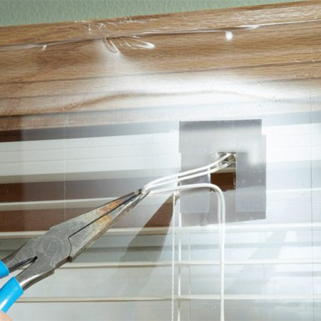 <b>Extract the lift cords</b></br> Pull the lifting cords out of the hole. Then you can raise and lower the blinds all winter with the shrink film in place.