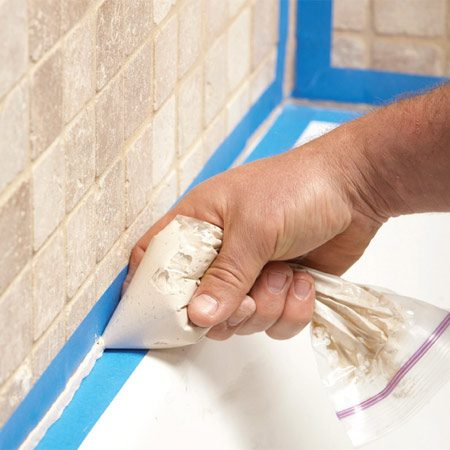 <b>Photo 2: It's like decorating a cake!</b></br> Scoop a hefty portion into a zip-top freezer bag. Zip the top shut and snip off one bottom corner. Then apply the caulk/grout bead to your tub and tool the joint with a plastic spoon or wet finger. Pull the tape free before the caulk sets up.