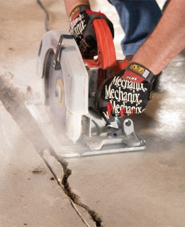 <b>Photo 1:  Cut a chiseling groove</b></br> Using a diamond blade on your circular saw, cut a 1/2-in.-deep groove along each side of the crack. Wear an N-95 respirator and turn on a fan to blow the concrete dust out of the garage. Chip out the cracked portion with a maul and cold chisel.