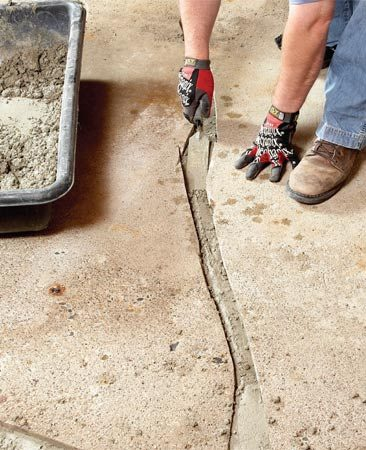 <b>Photo 3: Fill groove with concrete</b></br> Add latex modifier to regular concrete mix and pack it into the channel. Fill to within 1/2 in. of the original height. Let it set up for a few days, then fill with resurfacer.