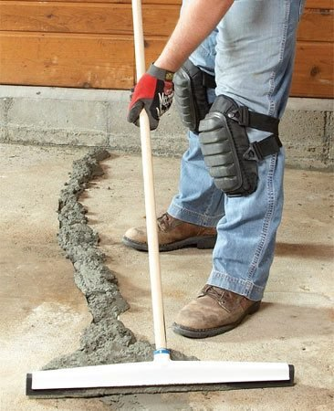<b>Photo 4: Spread the resurfacer </b></br> Pour concrete resurfacing mixture into the crack and smooth it out with a rubber floor squeegee. Feather the edges to get the best appearance.
