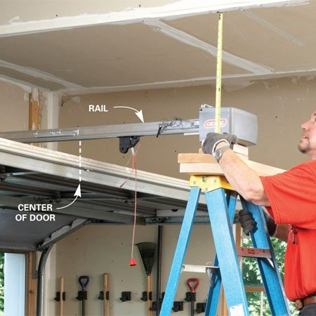 <b>Position the opener</b></br> Place the opener on a ladder and use scrap lumber to get it at  the height you need. Align the opener's rail with the center of the  garage door.