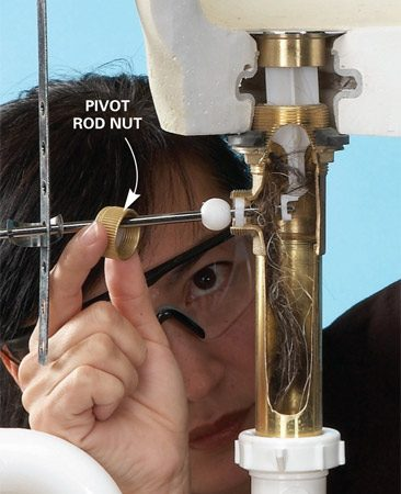 <b>Photo 3: Unscrew the pivot rod</b></br> Unscrew the pivot rod nut and pull out the rod. Lift out the stopper. Clean out the hair and reinstall the stopper and pivot rod.