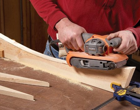 <b>Photo 4: Gang-sand the curves</b></br> Belt-sand the curved parts to eliminate saw marks and smooth out the curves. A belt sander works best, but an orbital sander will do the job too.