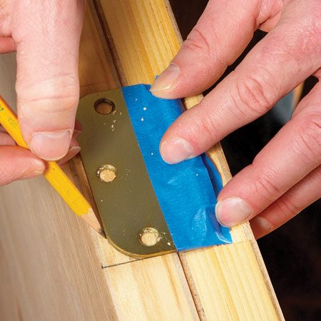 <b>Photo 3: Trace the hinge</b></br> Unscrew the hinge and tape it in place to trace the rest of the hinge outline. Be sure to match the distance from the edge of the door to the edge of the hinge (the same as it was on the old door).