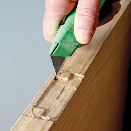 <b>Photo 4: Chisel and slice</b></br> Chisel out the opening, leaving the corners for last. Then use a sharp utility blade to score around the corner radius. Pop out the corner slug with the chisel.
