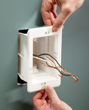<b>Photo 2: Insert the new box</b></br> Thread the old wires into the top or bottom clamp and pull on them until the cable jacket comes through. Slide the box into the opening and tighten the retaining tabs.