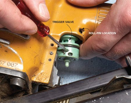 <b>Photo 3: Swap out the trigger valve</b></br> Locate the roll-pin driver tool and tap it out with a small hammer. Then pull out the valve and install the freshly greased replacement.