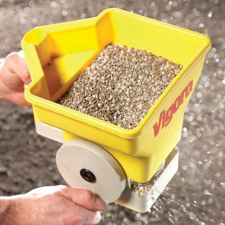 <b>Spread fertilizer</b></br> Spread a slow-release fertilizer on the garden using a handheld spreader for even coverage.