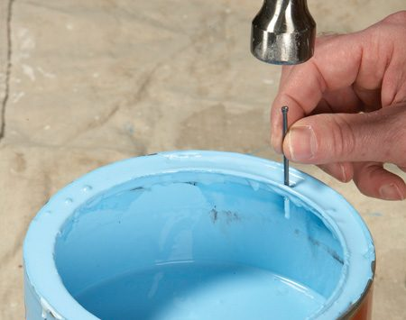 <b>Puncture and drain</b></br> Use a small nail to drive four holes in the rim of the paint can. Let the paint drain back into the can and seal the lid with a block of wood and a hammer.