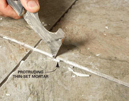 <b>Photo 1: Clean the joints</b></br> Vacuum the grout lines, then scrape any protruding grout and vacuum again. Don't scrape too hard or you may chip the tile glazing.