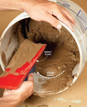"<b>Photo 4: Load the grout float</b></br> Tip the bucket toward you. Drag some grout ""up the slope,"" then scoop it onto the float."