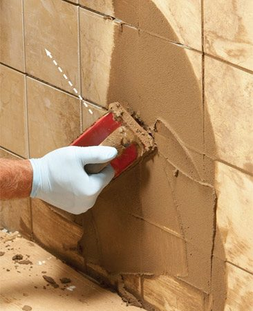 <b>Photo 5: Spread the grout</b></br> Smear the grout diagonally across the tile to force it deep into the joints and prevent it from being sucked back out as your float slides along.