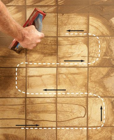 <b>Photo 6: Squeegee off the excess</b></br> Remove the bulk of the grout by wiping in a serpentine motion. This helps evenly distribute the grout and prevents the grout float edge from digging into grout lines.