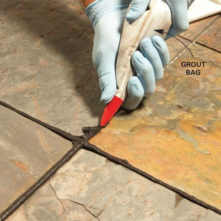 <b>Photo 2: Squeeze in the grout</b></br> Twist the bag like you're icing a cake to force the grout into each joint. This takes time, so only mix small batches until you get a feel for how much flooring to bite off at once.