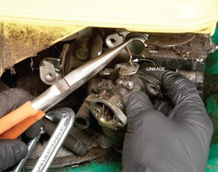 <b>Photo 2: The carb comes off easily</b></br> Use a socket or nut driver to remove the two bolts that hold the carburetor to the engine. Then unhook the throttle cable from the carburetor linkage.
