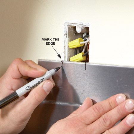 <b>Photo 3: Mark for an outlet cut</b></br> Hold the tile in position to mark both sides of the electrical box. Then remove the tile and measure the distance from the tile below to the bottom of the box and mark this on the tile.
