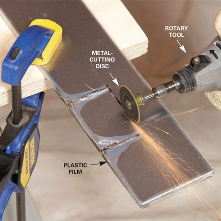 <b>Photo 4: Notch with a rotary tool</b></br> Clamp the tile and cut the notch. Cut notches with a rotary tool. Don't worry about the protective film on the tile; it will loosen along the cut, but it won't melt or burn.