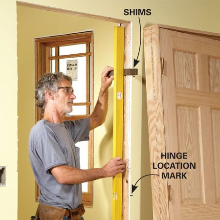 <b>Shim the easy way</b></br> Mark the location of the hinges on the drywall alongside the opening so you'll know where to place the shims. Place shims at the top and bottom hinge locations using a long level or a straight board and a short level. Then add the center shims.