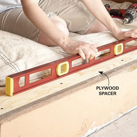 <b>Avoid clearance problems</b></br> Screw a strip of plywood to the bottom of the rough opening to raise the door and prevent it from rubbing on the floor inside.