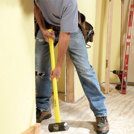 <b>Photo 2: Nudge the wall</b></br> Protect the wall with a 2x4 scrap while you move the bottom of the wall over with a sledgehammer. When the wall is plumb, toe-screw the bottom plate to the floor to hold it in place.