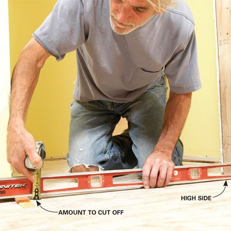<b>Photo 1: Check with a level</b></br> Level across the opening and shim up one side until the bubble is centered. The distance between the level and the floor tells you how much to cut off the jamb.