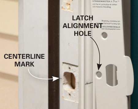 <b>Photo 3: Attach the jamb reinforcement plate</b></br> Extend the pencil marks to the door stop. Then line up the center of the latch alignment hole on the reinforcement plate with the centerline mark. Slide the plate into place. Predrill two holes and run the supplied screws <em>almost all the way</em> into the jamb with your drill. Stop before they're seated or you'll bow the door frame.