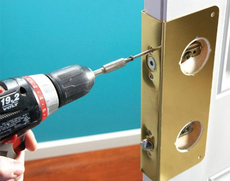 <b>Photo 1: Reinforce the door</b></br> Slide the reinforcement plate onto the door and insert the dead bolt and dead latch. Secure them with 1-1/2-in.-long stainless steel screws. Then secure the plate to the door with the matching screws from the kit.