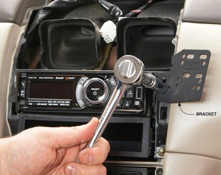 <b>Photo 1: Attach the bracket to the radio</b></br> Remove the trim bezel and one of the bolts that hold the radio in place. Then attach the bracket and reassemble.