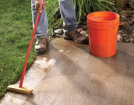 <b>Photo 1: Scrub the perimeter</b></br> Clean the edges of the patio where you'll later glue down the border pavers. Clean concrete means a stronger glue bond.