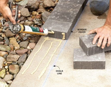 <b>Photo 2: Glue down the border pavers</b></br> After setting each paver, run a bead of construction adhesive up the side of it. That will keep the sand from washing out between pavers.
