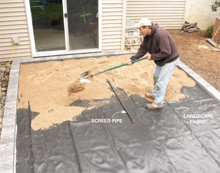 <b>Photo 3: Spread fabric, then sand</b></br> Lay down landscape fabric to keep the sand from washing down into cracks. Then position the screed pipe and spread the sand.