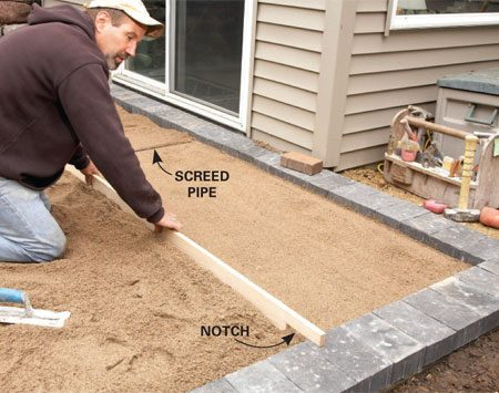 <b>Photo 4: Flatten the sand</b></br> Notch one end of a 2x6 to match the depth of the field pavers. The other end rides on the screed pipe. Screed both halves of the field, moving your screed pipe as you go.