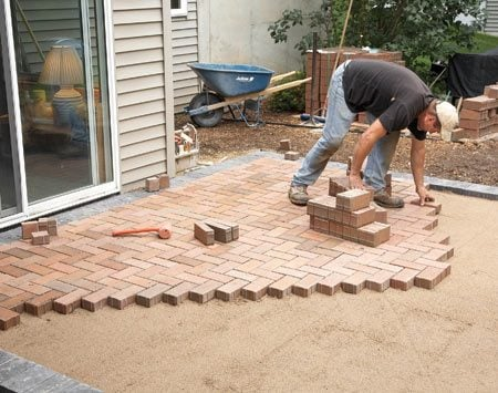 <b>Photo 5: Lay the pavers</b></br> Cover the sand with field pavers. When the field is complete, glue down the final border pavers. Then tamp the field with a plate compactor and sweep sand over the pavers to fill in the gaps.