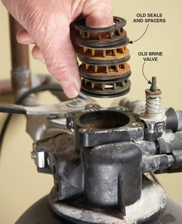 <b>Photo 2: Remove the valve innards</b></br> Stick your finger down into the control valve and pull out the four spacers and five seals. Toss them.