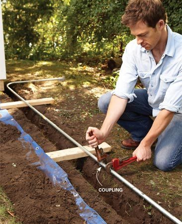 <b>Photo 4: Join the conduit</b></br> Assemble the conduit run aboveground to make tightening the connections easier. Support the conduit with 2x4s until youve connected all but the last section.