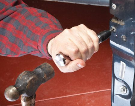 <b>Photo 2: Hold, smack, turn</b></br> Get a solid grip on the impact tool. Then smack the end with a hammer. The blow automatically forces the Phillips bit into the screw head and twists it at the same time.