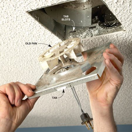 <b>Photo 2: Take out the old fan</b></br> Make sure the wall switch for the fan is turned off. Either remove the screw that holds the fan in place or push out on the metal fan housing to release the tab holding the fan. Then simply pull the fan down and unplug it.