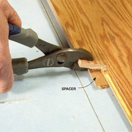 <b>Photo 1: Raise the floor to gain leverage</b></br> Slip a dowel or scrap piece of flooring under the seam. Grab the section with pliers and tilt it down until the glued seam cracks apart. Then snap it upward to break any remaining glue.