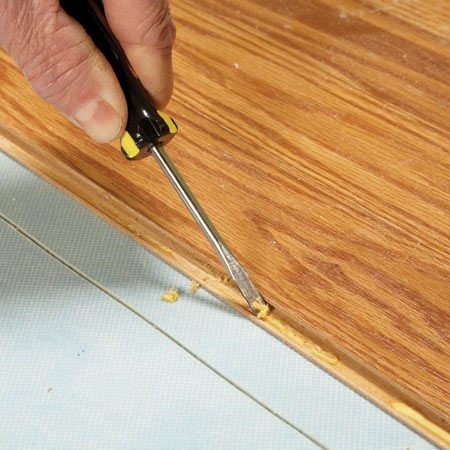 <b>Photo 2: The old glue has to go</b></br> Use a flat-blade screwdriver or small chisel to chip out the old glue. Get the surfaces as smooth as possible for a flush fit and a good glue bond.