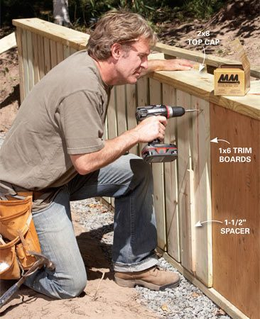 <b>Photo 6: Add the trim</b></br> Nail vertically oriented plywood to the top and bottom plates and to the front of the wall. Make sure to seam plywood over studs. Screw a 2x8 top cap to the top plate, hanging it over the front of the wall 1-1/2 in. Fasten vertical 1x6s to the sheathing with 1-1/2-in. spaces between boards.