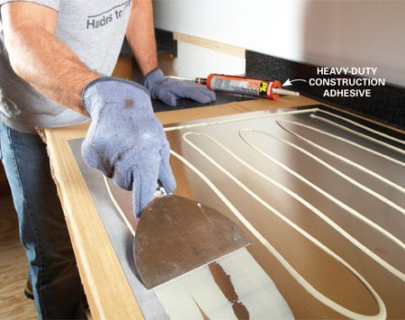 <b>Photo 1: Apply construction adhesive</b></br> Smooth the construction adhesive across the entire panel with a wide putty knife. Spread it evenly so you don't leave bumps that will show through the thin metal.