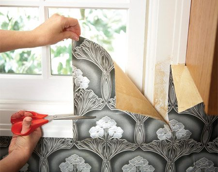 "<b>Photo 1: Cut out windows with scissors</b></br> Make ""relief cuts"" with a sharp scissors until the paper lies flat against the wall. Then use a razor to make the final cuts by following the contours of the molding."