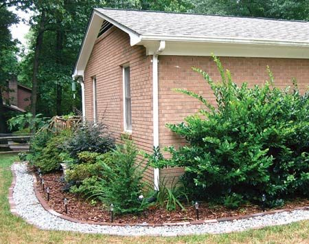 <b>House and drain system</b></br> A French drain around the corner of the house doubles as a path.