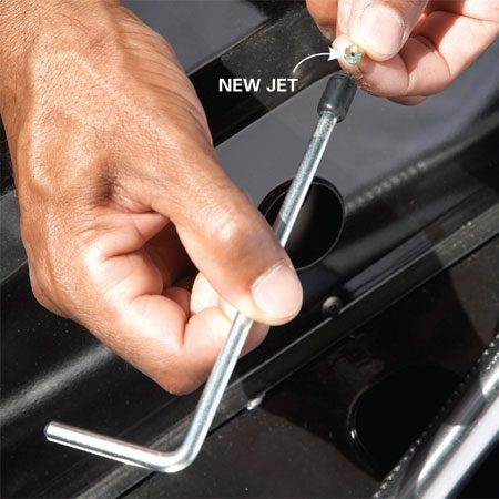 <b>Photo 1: Swap the jets</b></br> To remove the old jets, use the jet wrench that comes with the conversion kit (or a socket on an extension bar). Then install the proper jets for your grill model.