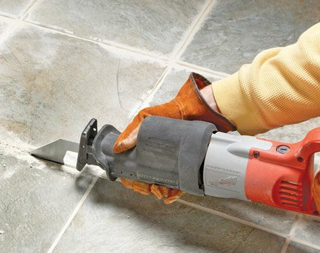 "<b>The recip saw method</b></br> Install the carbide-grit grout blade into your recip saw so it points down while the saw handle is pointing up. Apply power and ""saw"" out the grout."