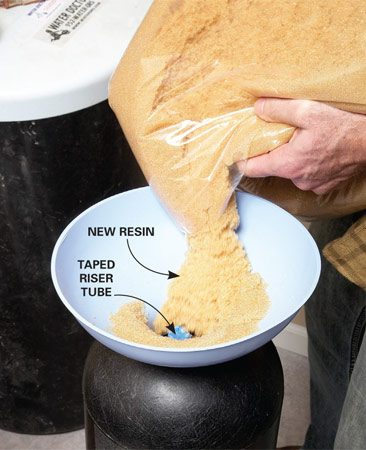 <b>Photo 3: Add new resin</b></br> Tape off the riser tube and position the funnel. Pour in the gravel and shake the tank to help it settle. Then have a friend help you pour the new resin into the funnel. It makes a huge mess if it spills.