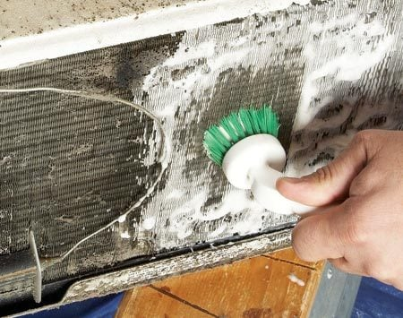 <b>Photo 3: Apply a foam cleaner</b></br> Shoot the spray over the entire surface of both coils and let the foam do the work for you. If the buildup is heavy, brush in the direction of the fins with a nylon-bristle brush.
